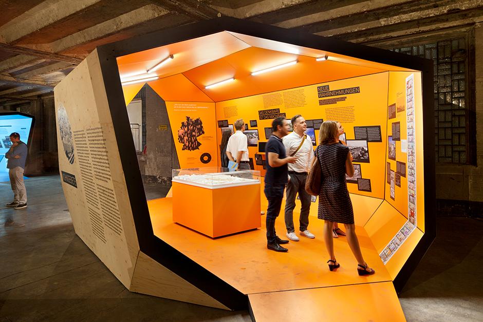 Ausstellungsarchitektur. Begehbarer Ausstellungskörper, Innen, orange. Mehrere Personen stehen vor Abbildungen.