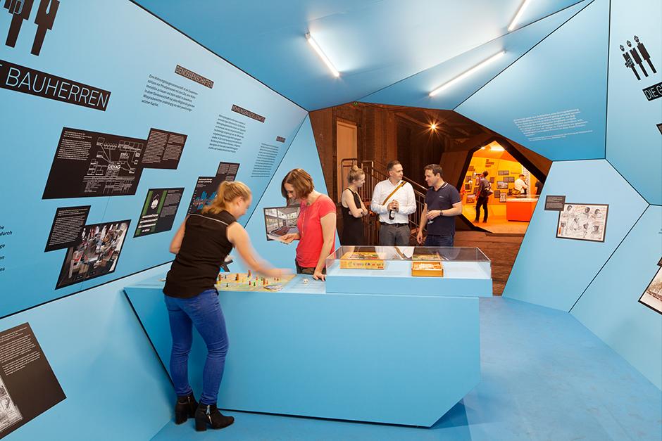 Ausstellungsarchitektur. Begehbarer Ausstellungskörper, Innen, blau. Personen spielen ein Spiel.