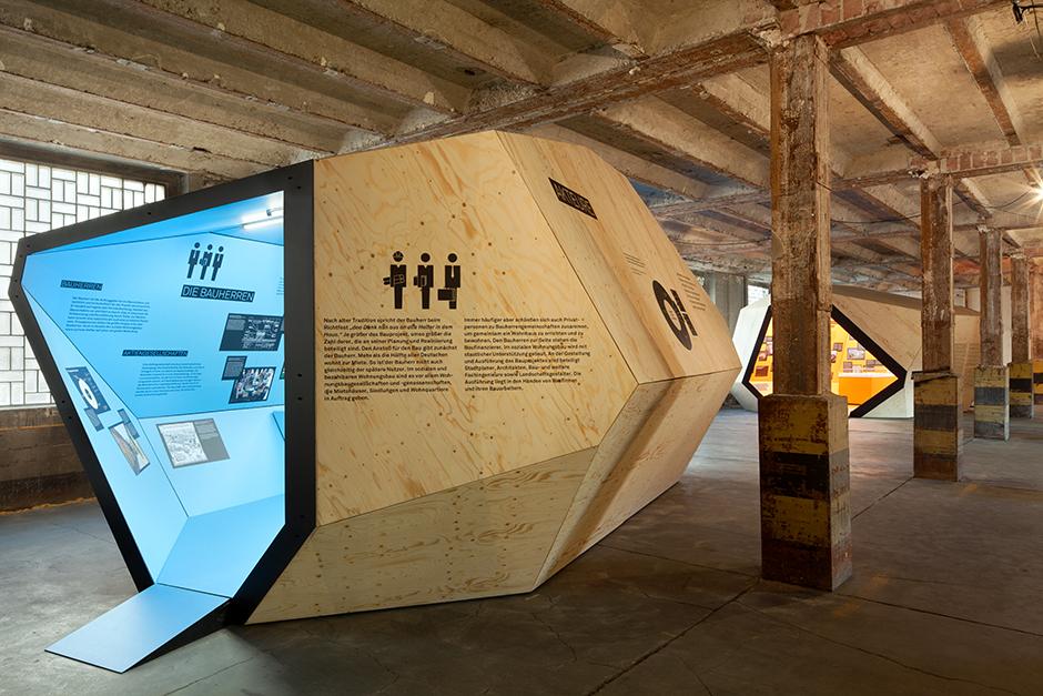 Ausstellungsarchitektur. Begehbarer Ausstellungskörper, Aussen. Holz, Innen blau, in Fabrikhalle.