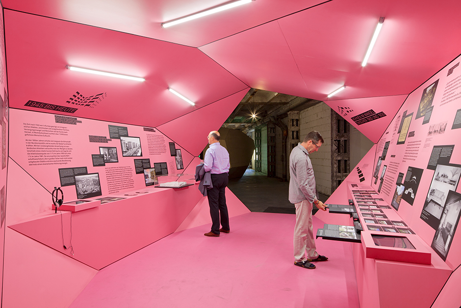 Ausstellungsarchitektur. Begehbarer Ausstellungskörper, Innen, rosa. Zwei Personen stehen an Vitrinen.