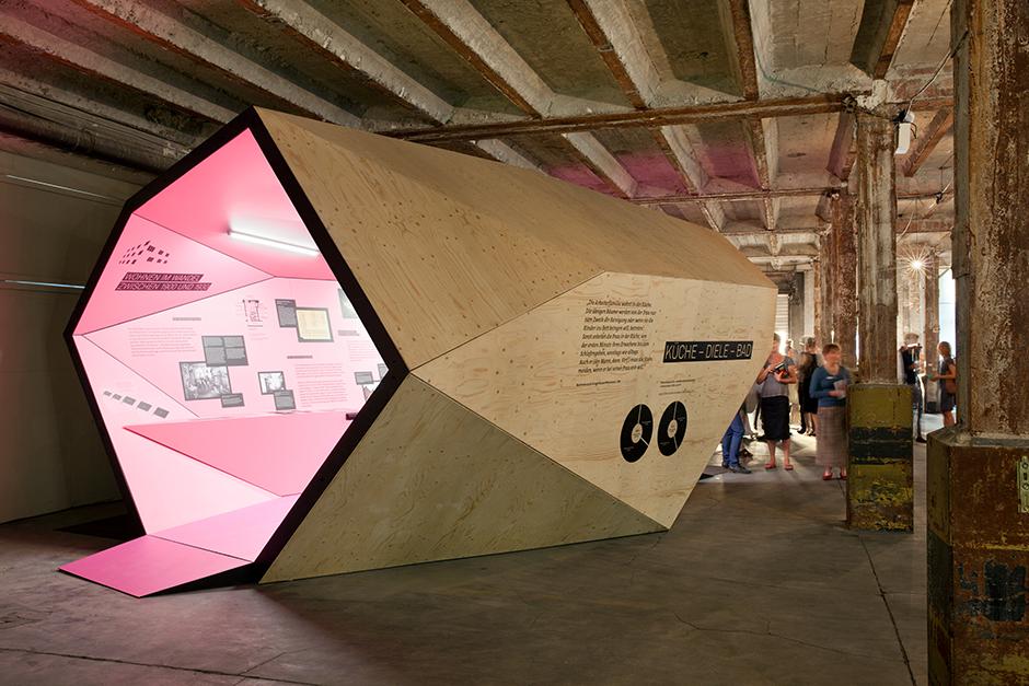 Ausstellungsarchitektur. Begehbarer Ausstellungskörper, Aussen. Holz, Innen rosa, in Fabrikhalle.