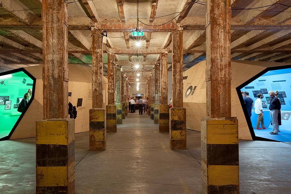 Ausstellungsarchitektur. Fabrikhalle mit Säulen und begehbaren Ausstellungskörpern.