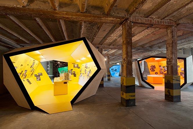 Ausstellungsarchitektur. Zwei Begehbare Ausstellungskörper, gelb und orange, in Fabrikhalle.