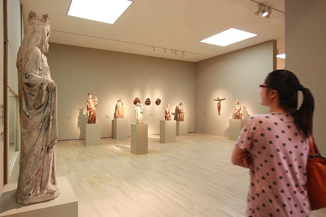 Museumsgestaltung. Besucherin betrachtet einen Ausstellungsraum mit alten Figuren.