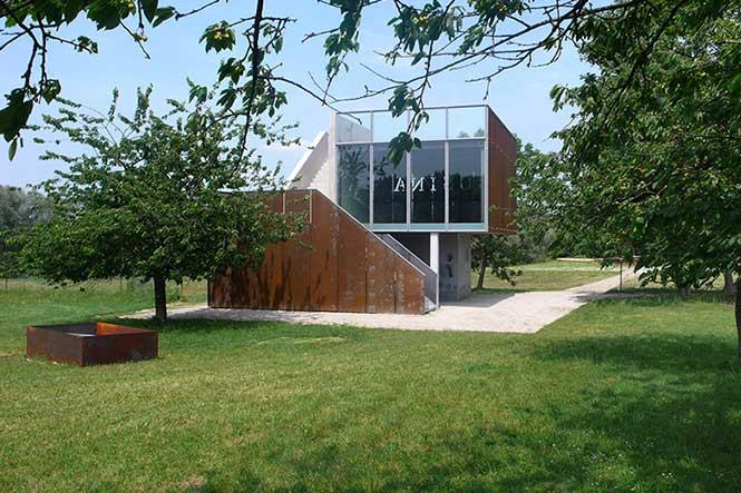 Ausstellungsarchitektur. Ausstellungsgebäude auf einer Wiese mit Bäumen.