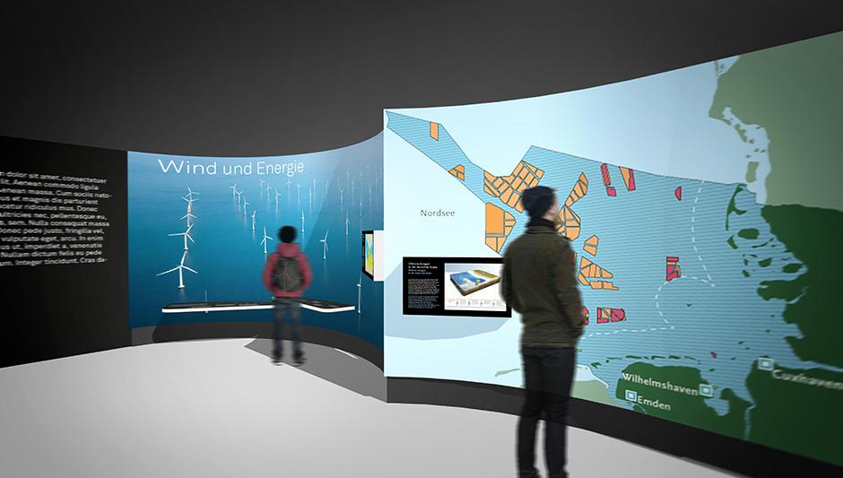 Szenographie. Besucher vor Ausstellungswand mit Windrädern.
